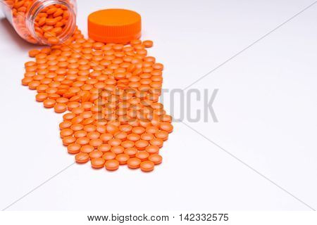 Medication pills spilling out onto a white surface. With room for text.