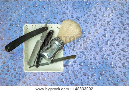 Two old razors and shaving brush on a colored background