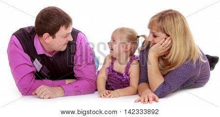 Happy family of three mom, dad and adorable little girl lying on the floor, and parents fondly looking on the beloved daughter-Isolated on white background
