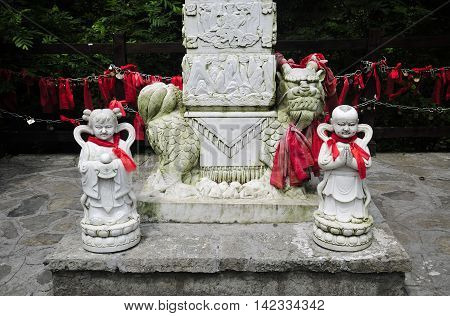 A buddhist tablet and statues on top of Tianmen Shan or Mount Tianmen in Zhangjiajie city in Hunan Province China.