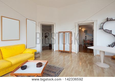 living room of old apartment, yellow divan and wooden floor