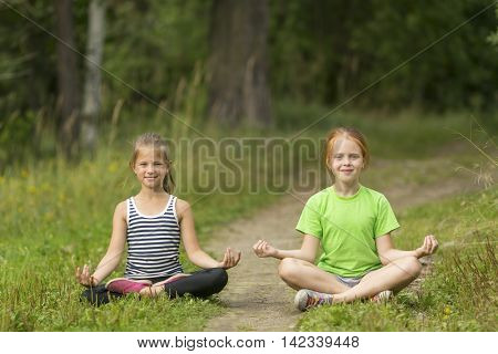 Two little cute girls sitting in the Lotus position in the Park. Yoga and a healthy lifestyle.