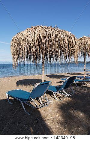 Straw umbrellas and sunbeds on a sandy beach Corfu Greece