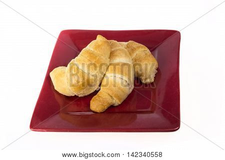 Three fresh flakey buttery croissants on a red plate and isolated on white.