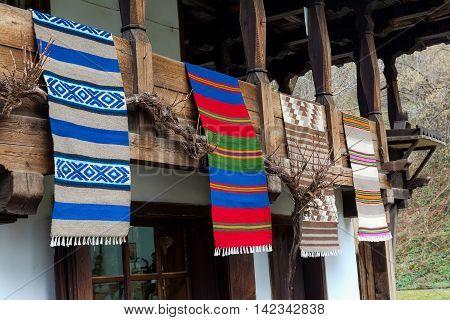 Traditional Bulgarian woven fabrics on the balcony of the wooden house in Etara village Bulgaria