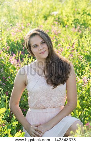 Portrait of a girl of 16 years in the flower meadow