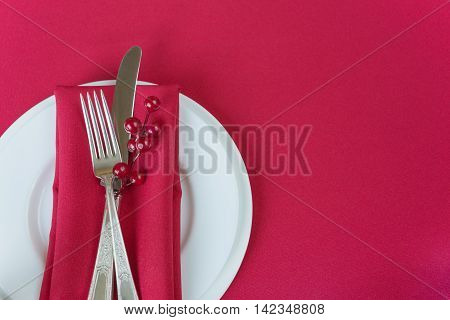 Silver knife and fork red linen napkin and red holly berries lie on the white porcelain plates which is located on a table covered with a red tablecloth; with space for text