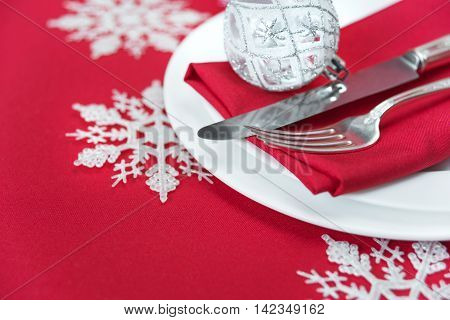 Christmas table: silver knife and fork red linen napkin and beautiful Christmas ball are on the white porcelain plate which is located on a table covered with a red tablecloth; with space for text