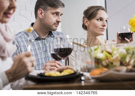 Man and woman are looking perplexed at someone during a family dinner