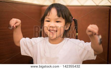 Asian Girl Holding Utensil ready to eat