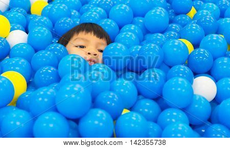 Asian Boy playing in a Ball pool