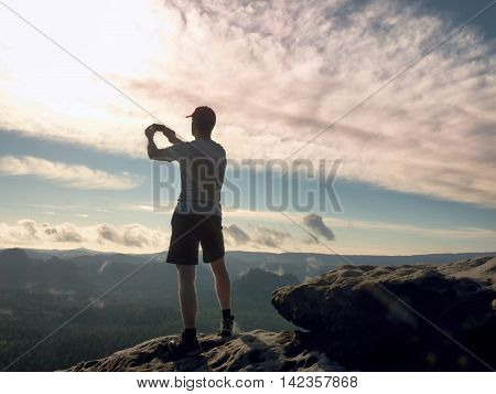 Man In Tshirt And Shorts Takes Photos With Smart Phone On Peak Of Rock Empire.