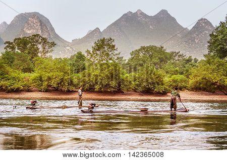 Yangshuo China - October 1 2008: Fisherman boats on Li river near Yangshuo Guangxi province China. Picturesque Karst mountains along the river.