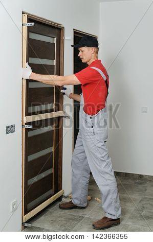 Installing door unit. Workman puting it into place.