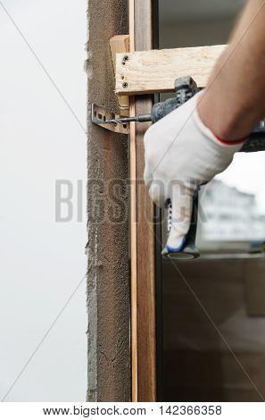 Installing door unit. Workman fixing the door frame using a drill.