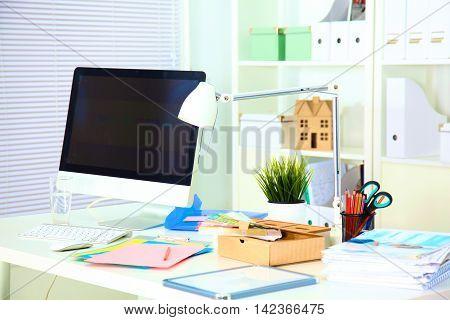 Designer working desk with computer and paperwork.