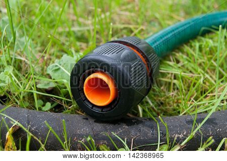 Close up image of water hose coupling in garden