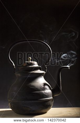 Old copper kettle on the black background.