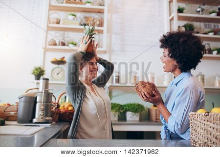 Juice bar employees playing with fruits at work. Young women holding coconut and pineapple while standing at bar counter.