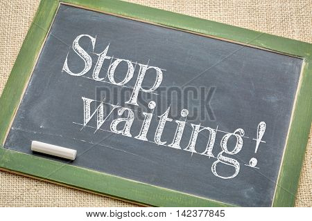 stop waiting advice  on a  vintage slate blackboard with a white chalk against burlap canvas