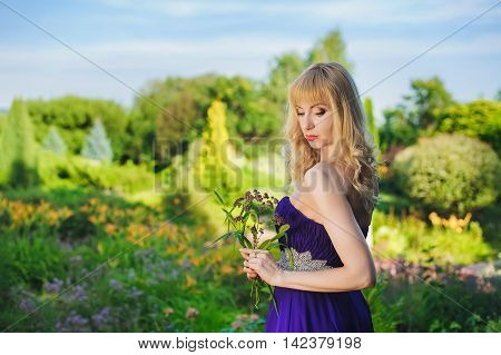 Portrait of beautiful woman dressed in evening gown. Blonde Beautiful woman in long purple dress like princess in green garden. Woman holding bouquet of wildflowers.