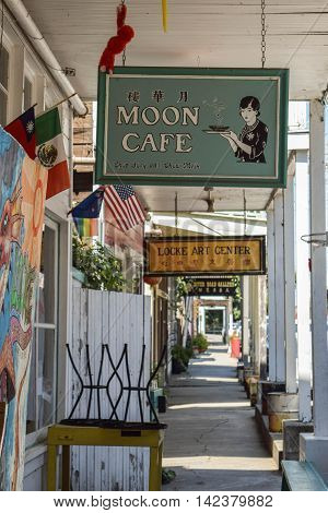 Locke, Ca, August 11, 2016: rustic store fronts and store signs down a long walkway, in the historic town of Locke, early afternoon, August 11, 2016