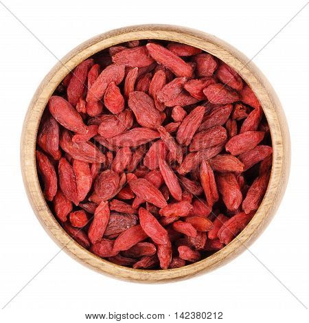 Goji berries in a bowl on white background, also called wolfberry. Dried red fruits and seeds of Lycium barbarum and Lycium chinense. Edible, raw and organic food. Isolated close up macro photo.