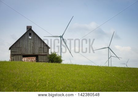Wind energy generator turbines in field with old weathered barn in foreground