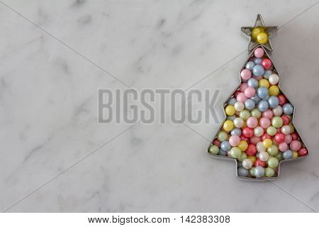 Christmas Tree Cookie Cutter Filled with Sugar Pearls on Marble Background Horizontal with Copy Space