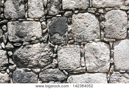 Walls details of a stone surface in an ancient Maya building in Chichen Itza, Mexico