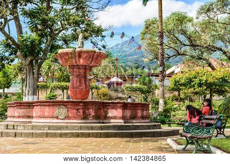 San Juan del Obispo Guatemala - June 24 2016: Fountain & St John's Day fair in village named after the patron saint on slopes of Agua Volcano. Near Antigua Guatemala's most famous Spanish colonial town & UNESCO World Heritage Site.