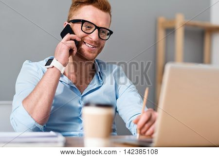 Get in Touch. Cheerful handsome smiling man sitting at the table and talking on cell phone while working