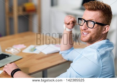 Like my work. Positive handsome delighted man sitting at the table and holding pencil while working