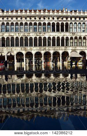 VENICE, ITALY - NOVEMBER 28: Reflection of Procuratie Vecchie in Saint Mark Square during 'Acqua Alta' (venetian high tide) NOVEMBER 28, 2015 in Venice, Italy