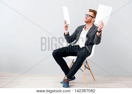Much work. Positive delighted smiling man sitting in the chair while working with papers
