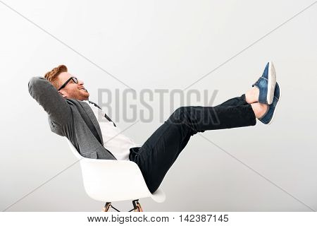 Have a nice rest. Overjoyed smiling content man holding his legs together and sitting in the chair while resting