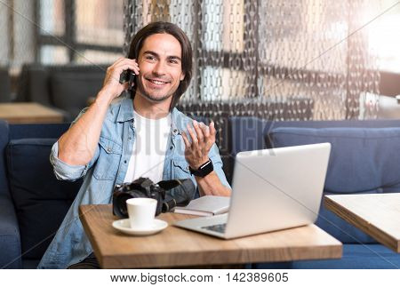 Call me back. Joyful smiling man talking on cell phone and sitting at the table while expressing gladness