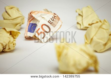 50 euro bill among crumpled office paper. Financial concept image.