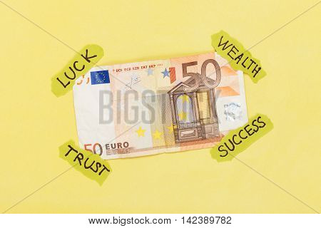 Euro banknote attached on yellow background with paper symbol sticks. Creative money concept