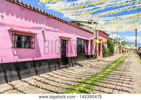 San Juan del Obispo Guatemala - June 26 2016: Houses adorned with balloons & bunting & pine needle carpets in street as part of St John's Day celebrations in village named after the patron saint. Near Antigua, a UNESCO World Heritage Site.