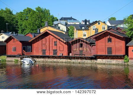 PORVOO, FINLAND - JUNE 13, 2015: Several old barns on the waterfront of the river Porvoyoki june evening. Historical landmark of the city Porvoo, Finland