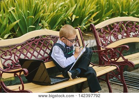 the boy in the glasses sitting with a laptop pre-school education