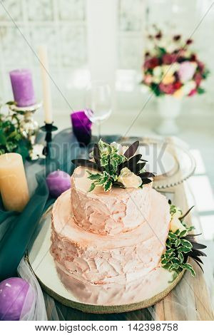 Beautiful wedding cake with flowers on wooden table with сandle