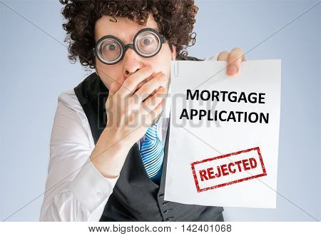Disappointed Man Is Showing Paper With Denied Loan Application.