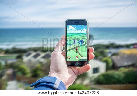 Male Hand Holding Iphone 6 With Pokemon Go In Residential Area Facing Ocean