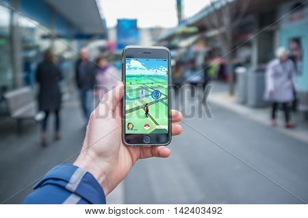 Male Hand Holding Iphone 6 With Pokemon Go On A Busy Street