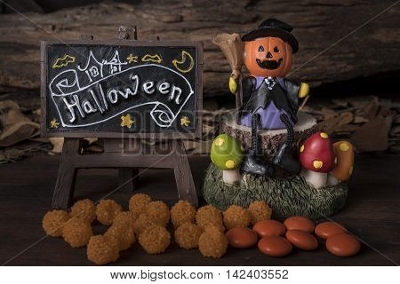 Pumpkin head jack (Jack-o-lantern) in witch suit sitting on a tree with halloween board and orange candy over forest background