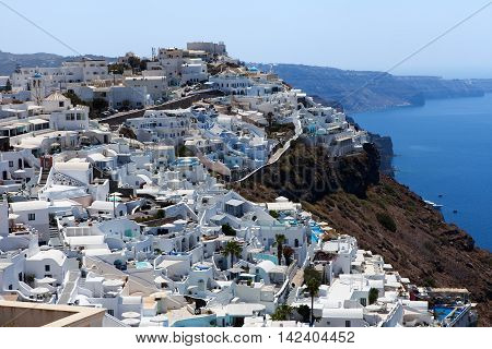 White houses and blue domes of Fira, Santorini at sunset
