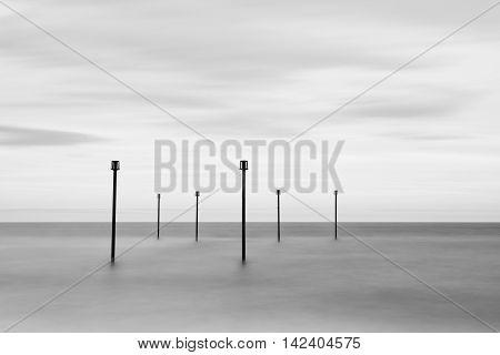 Minimalist landscape of calm sea wi5th sentinel warning posts