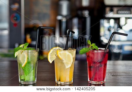 Three different refreshing lemonade with lemon and lime on a background of the bar in the cafe. Summer drink.